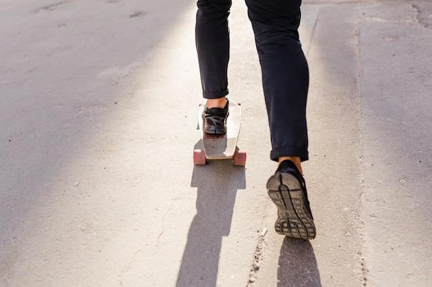 Vista in sezione bassa dei piedi di una persona che pattina sullo skateboard di legno