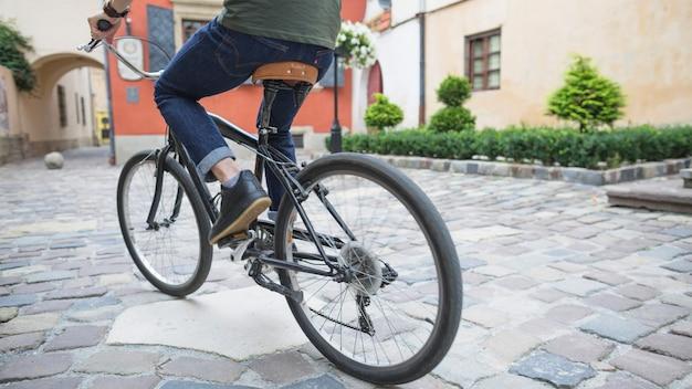 Vista in sezione bassa di un ciclista che guida la bicicletta sul marciapiede