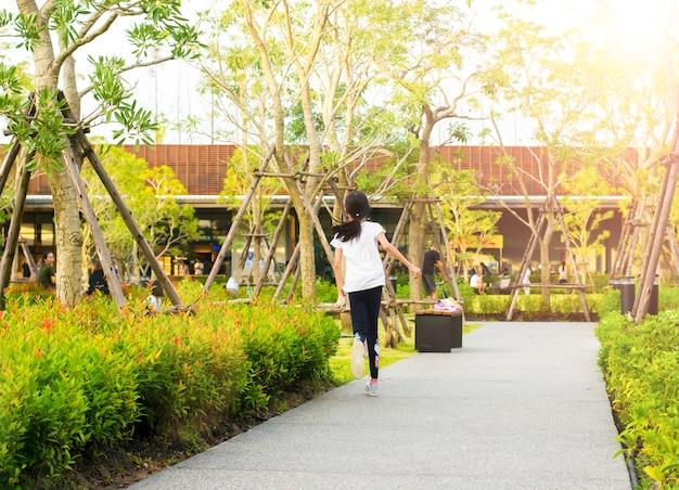Vista indietro la bambina è corsa sulla strada nel parco