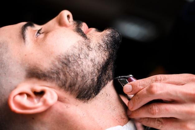 Vista laterale barbiere che rade il primo piano della barba del cliente