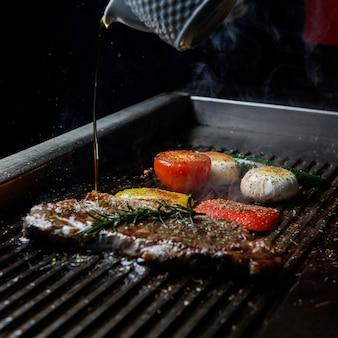 Vista laterale bistecca alla griglia con rosmarino e olio e funghi nel barbecue