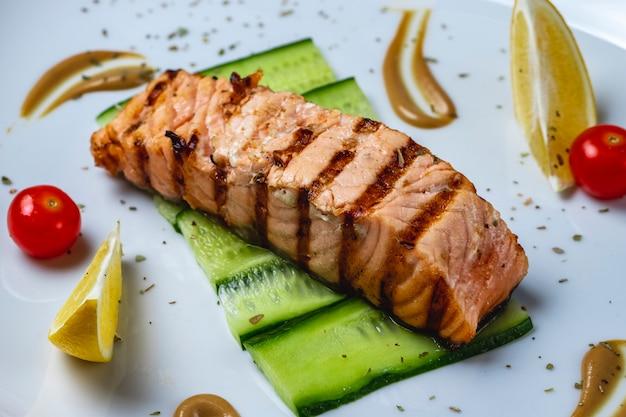 Vista laterale bistecca di pesce alla griglia con fette di pomodoro limone e cetriolo su un piatto
