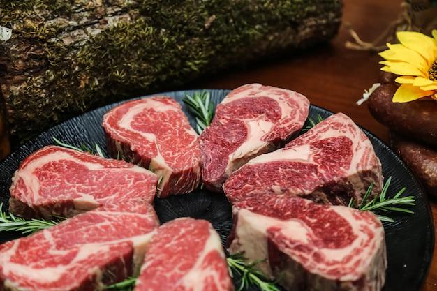 Vista laterale carne di bistecca marmorizzata cruda con rosmarino su un supporto