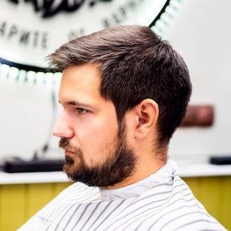Vista laterale cliente in attesa di un taglio di capelli