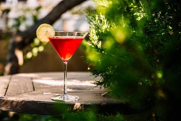 Vista laterale cocktail cosmopolita con liquore e fetta di limone