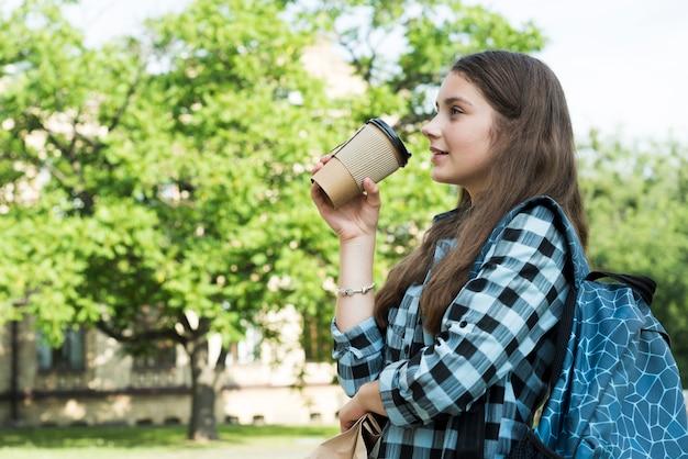 Vista laterale colpo medio adolescente che beve da papercup
