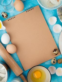 Vista laterale degli alimenti come tuorlo d'uovo con acqua e matterello su fondo blu con lo spazio della copia