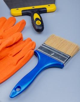 Vista laterale degli strumenti della costruzione come coltello del mastice dei guanti e pennello su fondo grigio