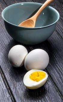 Vista laterale degli uova sode con una ciotola su fondo rustico di legno