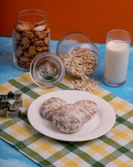 Vista laterale dei biscotti del pan di zenzero su un piatto bianco e una taglierina a forma di stella del biscotto sul tavolo da cucina