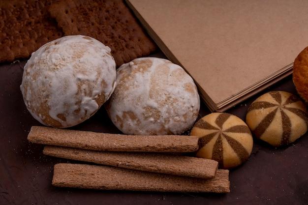 Vista laterale dei biscotti e dei biscotti croccanti dei biscotti del pan di zenzero su buio