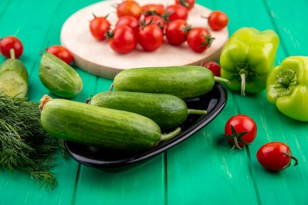 Vista laterale dei cetrioli nell'aneto del pomodoro del pepe e della ciotola intorno su superficie verde