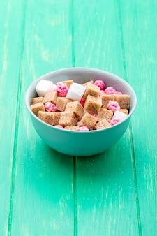 Vista laterale dei cubi dello zucchero bruno con le caramelle rosa in una ciotola su verde