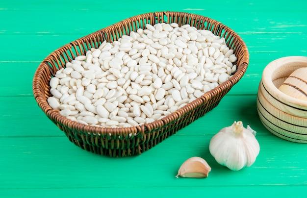 Vista laterale dei fagioli bianchi in cestino di vimini ed aglio sulla tavola di legno verde
