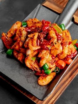 Vista laterale dei gamberi fritti con peperoni rossi e verdi su un tagliere di legno