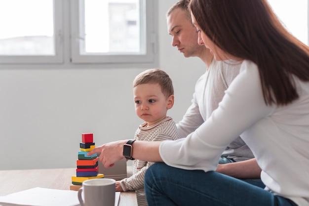 Vista laterale dei genitori con bambino che gioca a casa