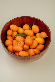 Vista laterale dei kumquat maturi freschi in una ciotola di legno su bianco