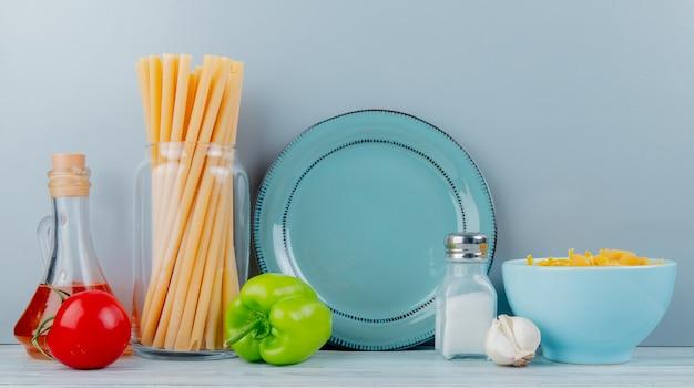 Vista laterale dei maccheroni come bucatini e altri con il sale e il burro di aglio del pepe del pomodoro con il piatto su superficie di legno e su fondo blu