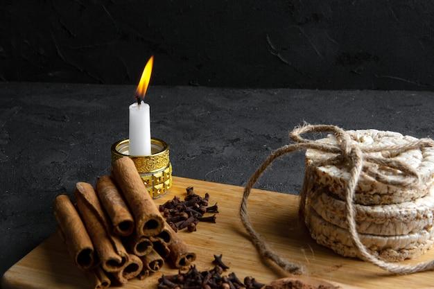 Vista laterale dei pani di riso legati con la corda e il bastoncino di cannella con una candela bruciante sul bordo di legno sul nero