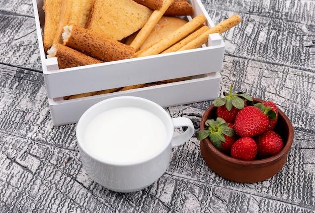 Vista laterale dei pani tostati con latte in cassa e fragola sull'orizzontale di superficie bianco