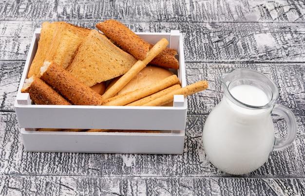 Vista laterale dei pani tostati con latte in cassa sull'orizzontale di superficie bianco