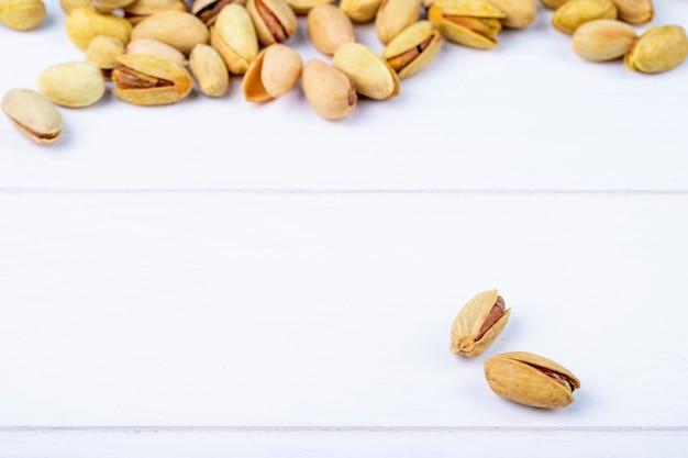 Vista laterale dei pistacchi arrostiti salati su fondo bianco con lo spazio della copia