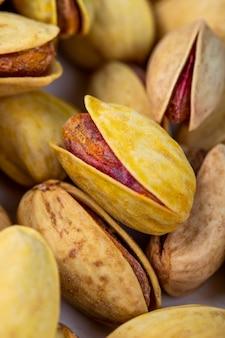Vista laterale dei pistacchi arrostiti salati su fondo bianco