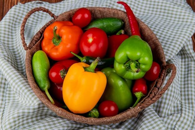 Vista laterale dei pomodori e dei cetrioli dei peperoncini peperoni dolci variopinti degli ortaggi freschi in un canestro di vimini sul tessuto del plaid