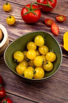 Vista laterale dei pomodori gialli in ciotola con quelli rossi su legno