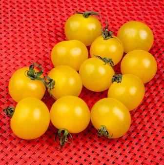 Vista laterale dei pomodori gialli sulla superficie rossa del panno