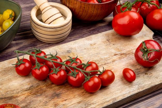 Vista laterale dei pomodori sul tagliere con altri un frantoio di aglio sulla tavola di legno