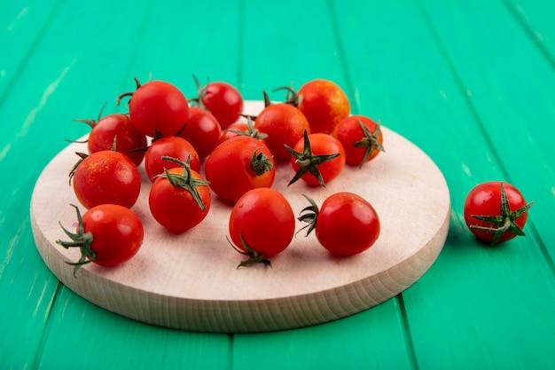 Vista laterale dei pomodori sul tagliere sul verde