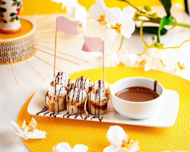 Vista laterale dei rotoli del pancake con panna montata e cioccolato su giallo