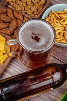 Vista laterale dei vari spuntini della birra patatine fritte e mini salatini con un boccale di birra su rustico