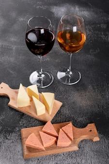 Vista laterale dei vetri e del formaggio di vino sul tagliere di legno sul verticale scuro