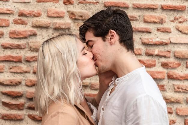 Vista laterale del baciare delle coppie