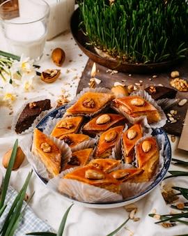 Vista laterale del baklava tradizionale dei biscotti di festa dell'azerbaigian sul rustico con le noci