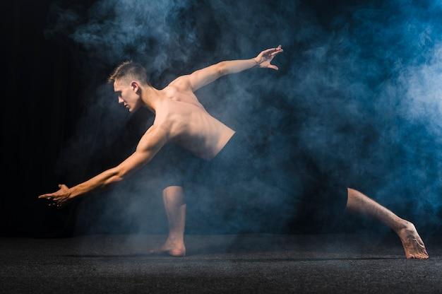 Vista laterale del ballerino che posa nel fumo