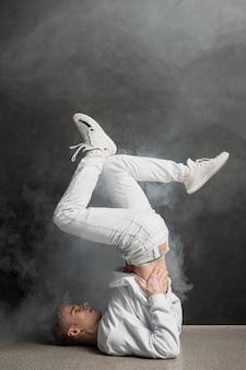 Vista laterale del ballerino maschio nella posa di ballo con fumo