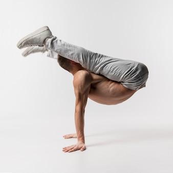 Vista laterale del ballerino maschio senza camicia nella posa delle scarpe da tennis
