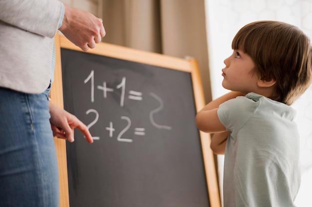 Vista laterale del bambino a casa a cui viene insegnata la matematica