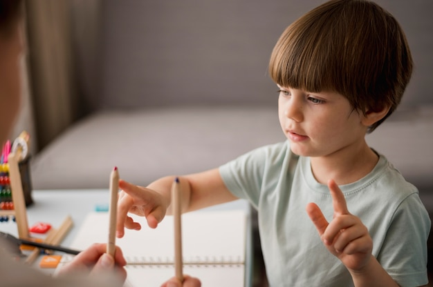 Vista laterale del bambino che impara come contare a casa usando le matite