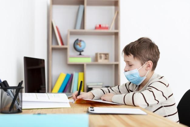 Vista laterale del bambino che indossa maschera medica e fare i compiti