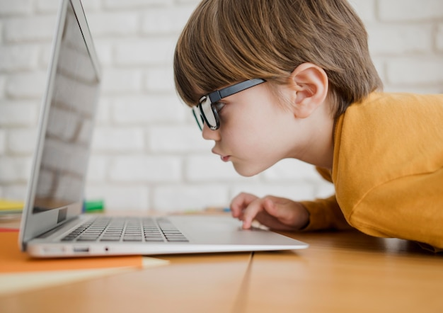 Vista laterale del bambino con gli occhiali avvicinarsi troppo per vedere il computer portatile