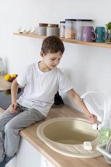 Vista laterale del bambino lavarsi le mani