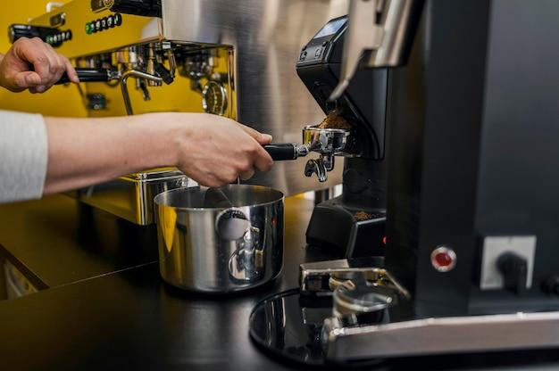 Vista laterale del barista che produce caffè alla macchina