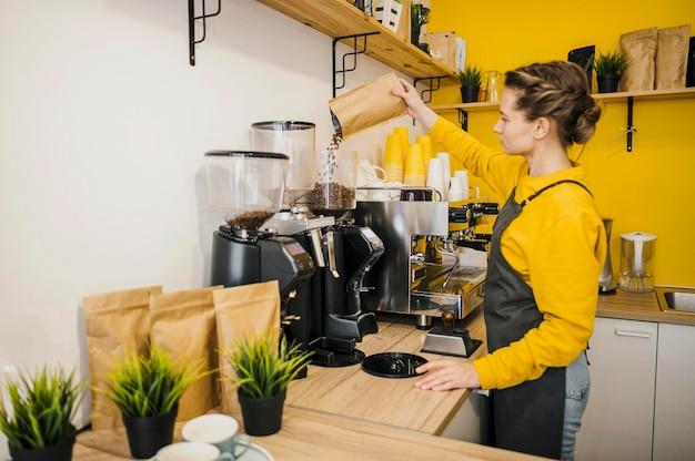 Vista laterale del barista macinare il caffè