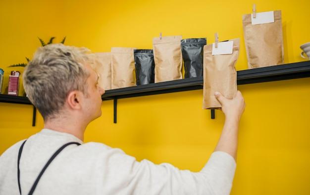 Vista laterale del barista maschio in caffetteria