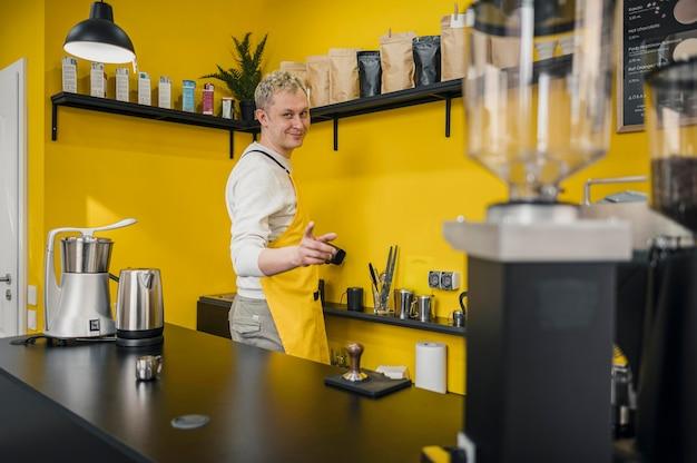 Vista laterale del barista maschio in negozio