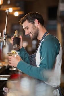 Vista laterale del barista sorridente che produce bevande